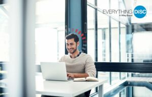 homem sentado à mesa escritório olhando laptop